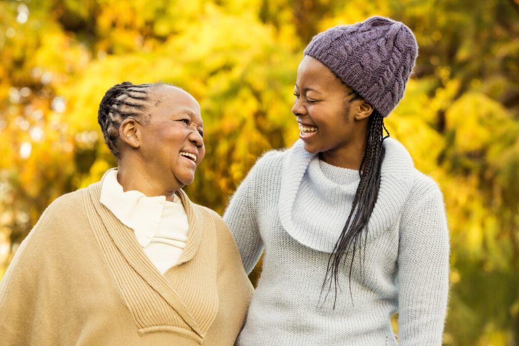 Photo of a Black woman and her daughter outdoors, smiling at one another.