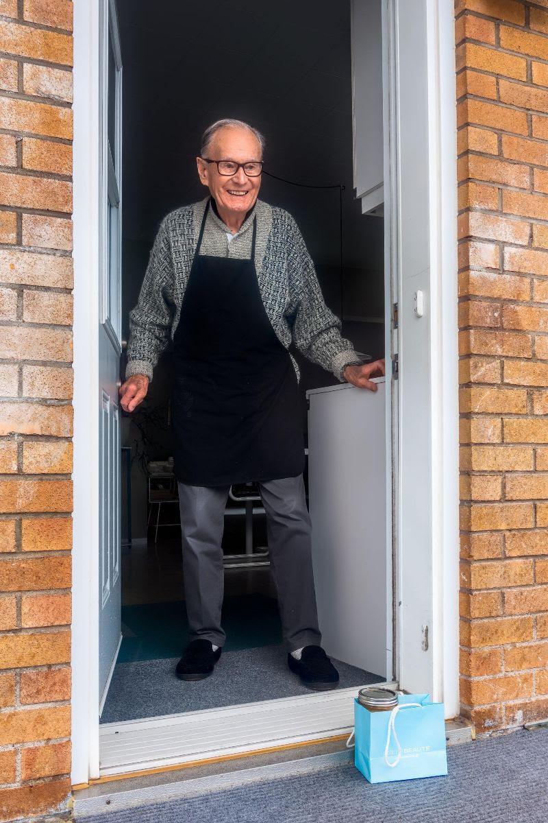 Elderly man standing at front door of home